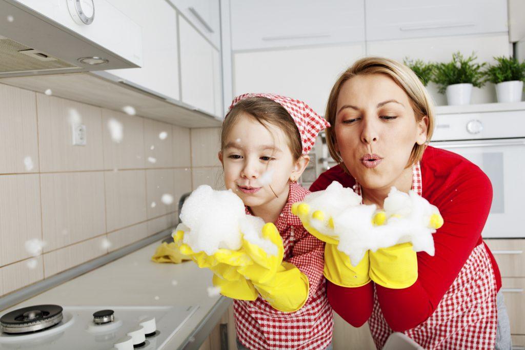 enseñar a los niños a ser ordenados: imagen de una madre jugando con la espuma de fregar con su hija