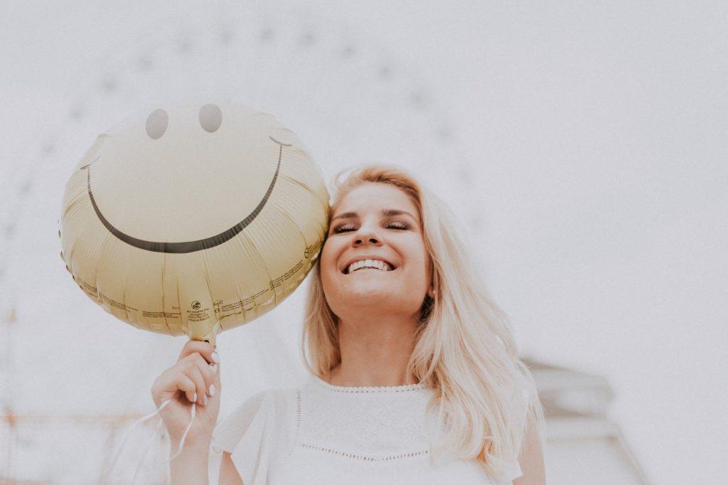 """Imagen para ilustrar la importancia del pensamiento positivo en el artículo sobre """"Como alcanzar el éxito"""". se ve una mujer sonriendo mientras sostiene un globo con el dibujo del emoji sonriente"""