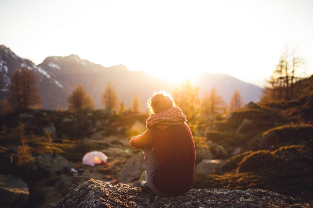 meditación consciente: imagen de una chica sentada de espaldas en un entorno de naturaleza